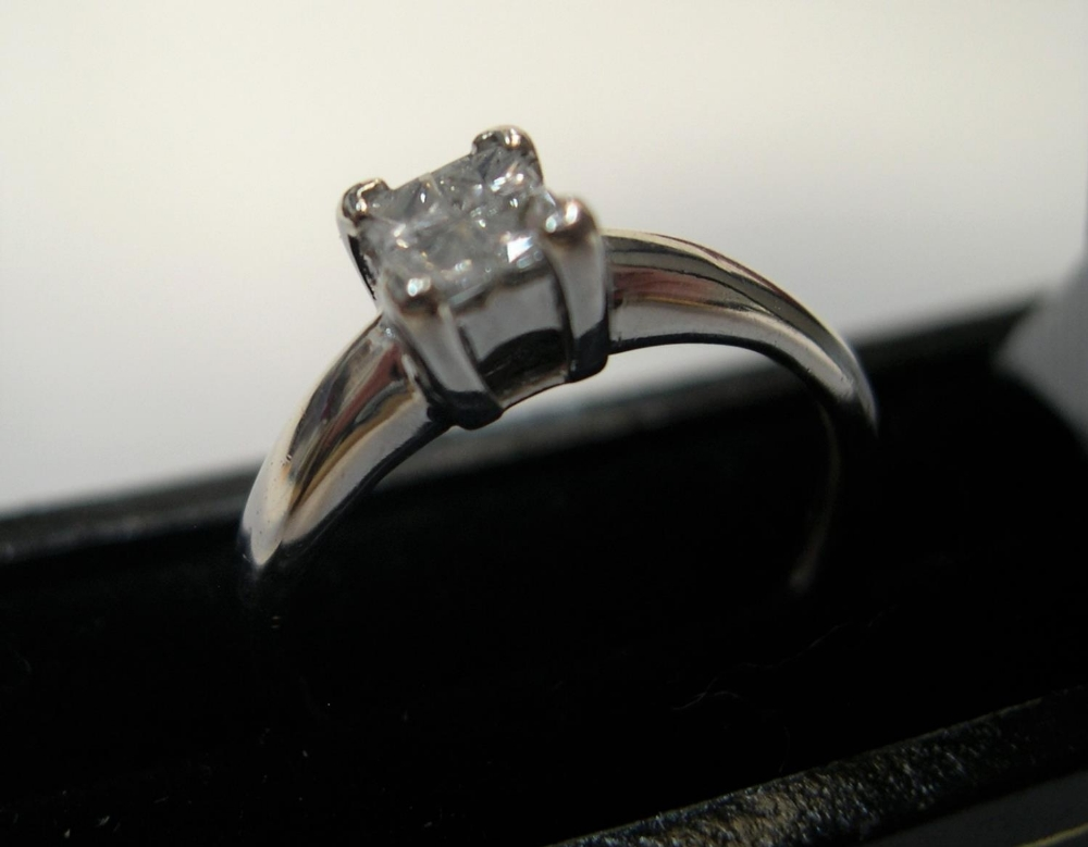 18ct white gold & diamond ring with 4 princess cut diamonds, rubbed marks. Approx 2.7 grams gross,