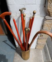 Collection of mainly brass topped walking sticks in brass holder (Qty)