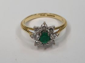 18ct yellow gold ring set with an oval cut Emerald surrounded by 8 round cut diamonds, each