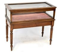 A 19th century style bijouterie table with glazed lift-up top and side panels with mirrored back