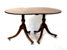 A Regency-style mahogany D-end twin pedestal dining table with one extra leaf,