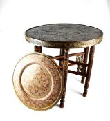 A 19th century circular Indian metal ornate table on a collapsible mother of pearl inlaid hardwood