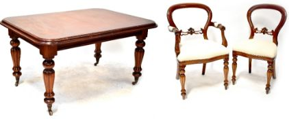 A Victorian-style mahogany wind-out dining table on bulbous turned and carved legs with castors,