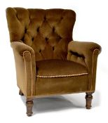 A 1930s walnut button-back armchair upholstered in brown velour and on turned feet.