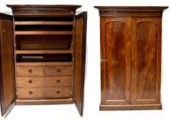 A Victorian mahogany linen press, two doors with arched raised panels,