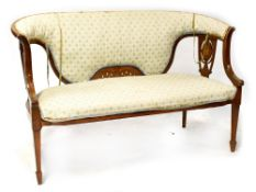An Edwardian inlaid mahogany bowed two-seater settee with upholstered back and pierced vase splats,