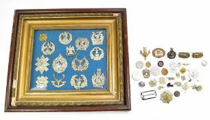 A group of predominantly regimental cap badges, some presented in glazed frame, with further loose