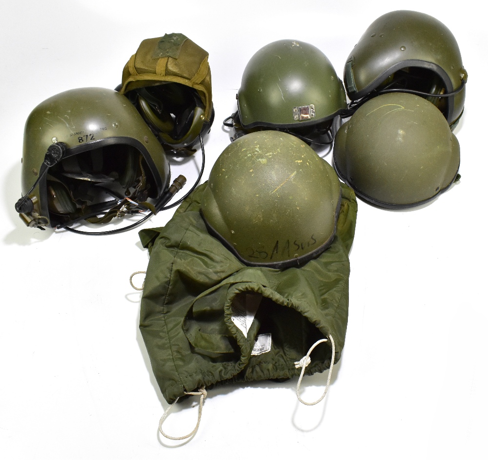Four armoured vehicle crew helmets, three with fitted headphones and communication accessories,