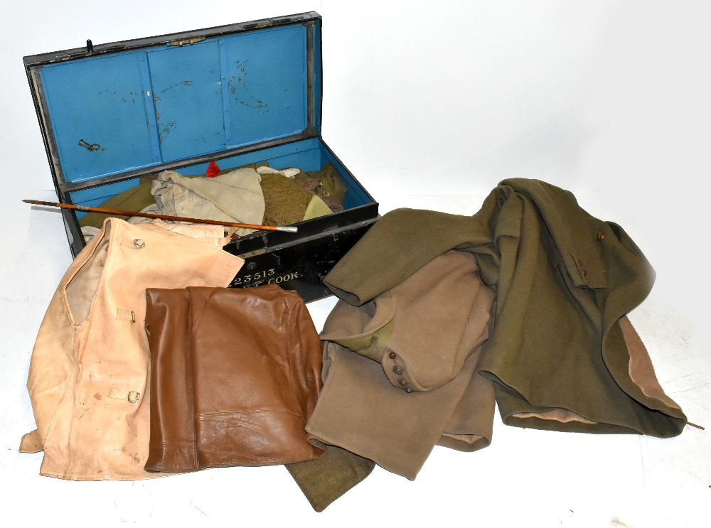 A collection of military uniform and accessories including two woolen great coats, two leather
