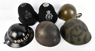 Four WWII and later military helmets, Brodie-type repainted with police decal, a police helmet (