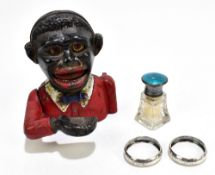 A cast iron 'Little Joe' novelty money box, height 13cm, two hallmarked silver napkin rings and a