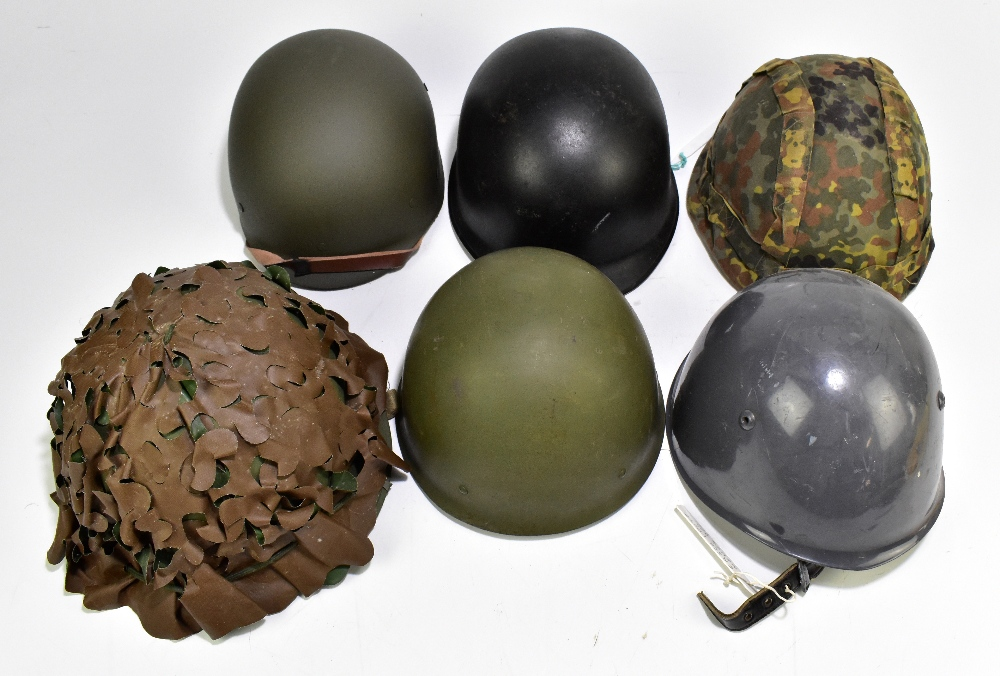 Five military and public service helmets comprising German Army M62 1A1, Italian Serbian Police,
