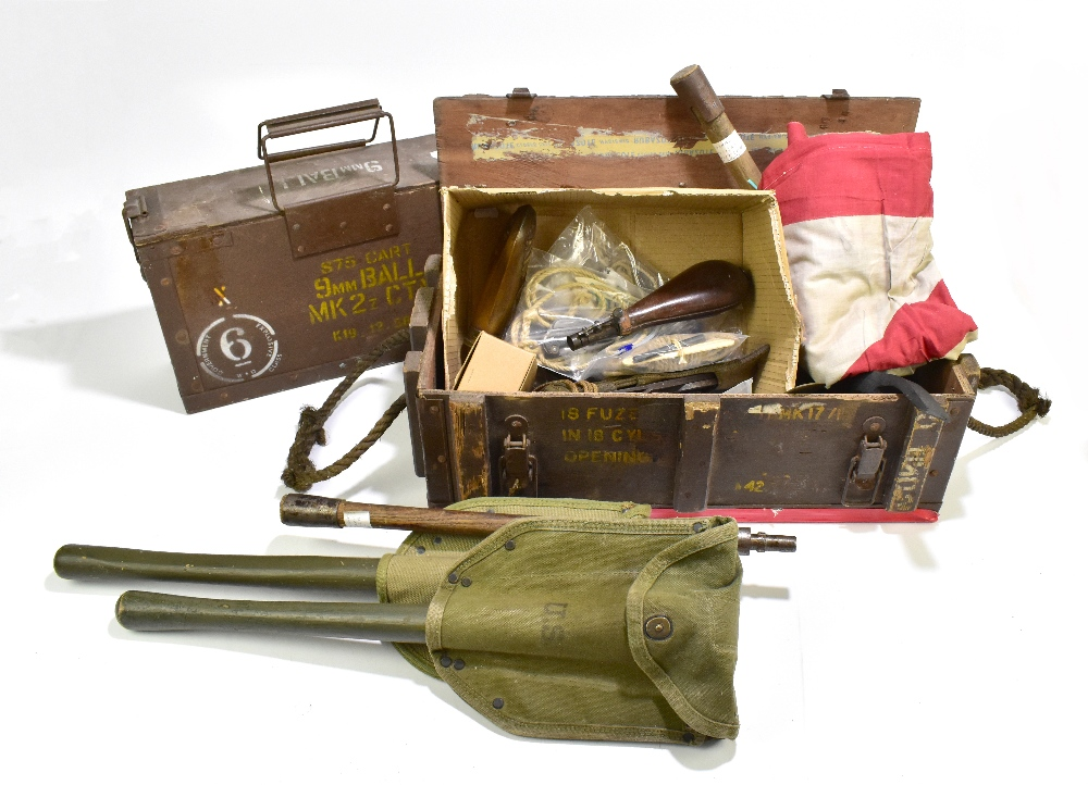 A mixed group of military equipment including entrenching tools, rope pulls, button guards, a