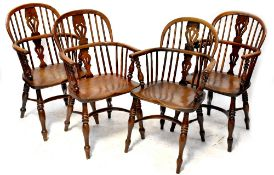 A set of four 18th century yew Windsor chairs with pierced splat backs flanked by simple spindle