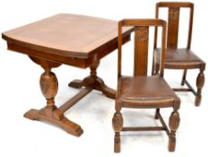 An early 20th century oak dining suite comprising a draw leaf table,