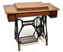 A Jones treadle sewing machine and table, oak top with hinged lid enclosing machine,