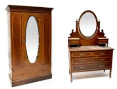 An Edwardian inlaid mahogany mirrored wardrobe with single door over a long drawer,