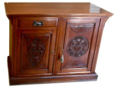 An Edwardian walnut sideboard with single drawer and two carved panel doors, on plinth base,