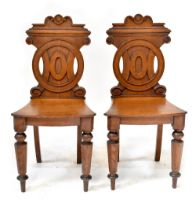 A pair of 19th century oak hall chairs, the backs with carved circular motifs,