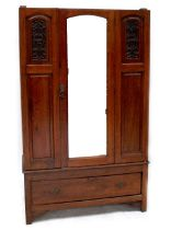 An Edwardian mahogany single mirrored door wardrobe, carved floral panel to either side of door,