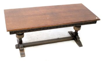 A JC reproduction oak coffee table with carved apron on bulbous stretchered supports,