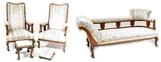 An early 20th century oak parlour suite comprising chaise longue with curved and upholstered rail,