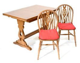 A 20th century oak draw-leaf table with country-style carved slab end supports to cross-stretcher,