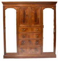 An Edwardian inlaid mahogany triple compactum wardrobe with pair of cupboard doors enclosing a