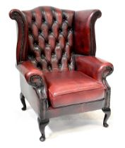 A modern button back wing armchair upholstered in oxblood studded leather, on cabriole legs.