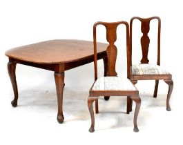 An early 20th century oak extending dining table with one extra leaf, on cabriole legs,