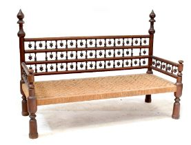An Indonesian hardwood settee with bobbin turned supports and rush woven seat, on turned legs,