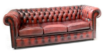 A modern Chesterfield three-seater sofa upholstered in oxblood studded leather, width 195cm.