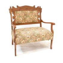 An Edwardian oak-framed settee of small proportions with carved back rest and upholstered in a