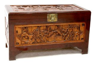 A Chinese camphor wood blanket box with carved panels depicting figures within landscapes,