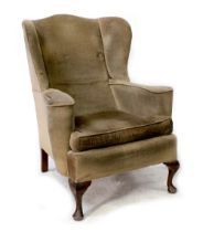 A George III style wing back armchair with outswept arms, upholstered in a mustard-coloured velvet,