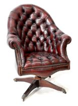 A modern red leather studded button back office chair on a swivel quadripartite base with castors.
