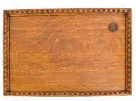 An early 20th century oak serving tray with carved border and inset King George VI Coronation