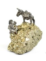 A small specimen of iron pyrite (fool's gold) surmounted with a small cast metal figure of a gold