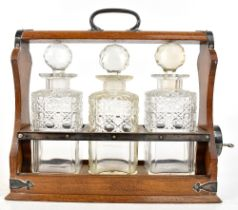 WALKER & HALL; an oak tantalus with silver plated mounts, housing three hob nail cut decanters,
