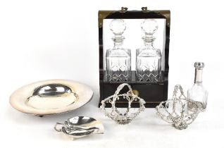 A modern mahogany effect brass bound tantalus enclosing two decanters, a pair of silver plated