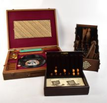 An English made cased games compendium housing a Roulette wheel, chess pieces, checkers, chess
