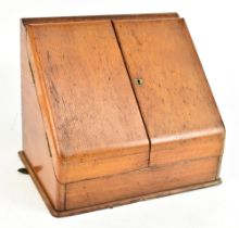 An early 20th century light oak stationery cabinet, the hinged doors enclosing fitted