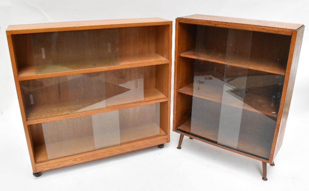 An oak bookcase with three sliding glass doors on castors, height 91cm, width 91.5cm, depth 22cm,