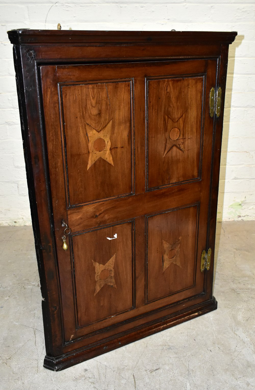 An 18th century oak corner cupboard, with inlaid detail to the single door, enclosing three shelves,