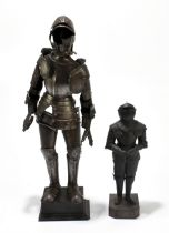 A miniature mock steel suit of armour on wooden stand, height 43.5cm, also a smaller example (2).
