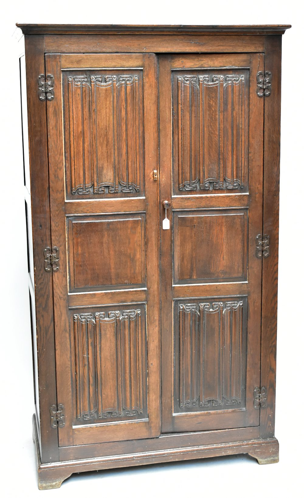An early 20th century oak wardrobe, the pair of linen fold carved doors enclosing rail, raised on