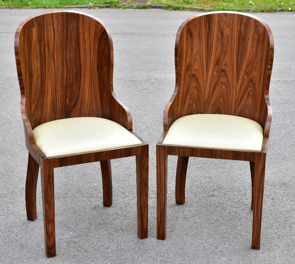 A pair of Art Deco rosewood veneered chairs, with drop-in seats, raised on block supports (2).
