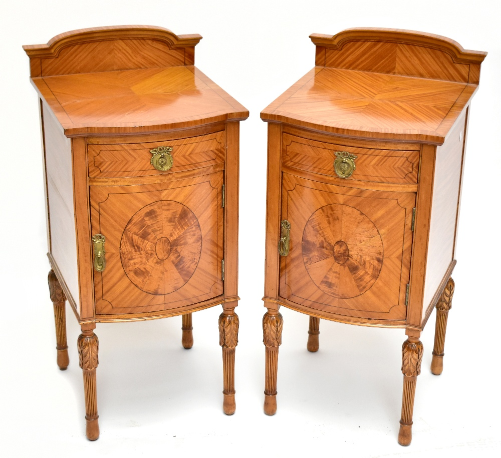 A pair ofEdwardian Sheraton Revival painted satinwood bowfront bedside cabinets, with raised