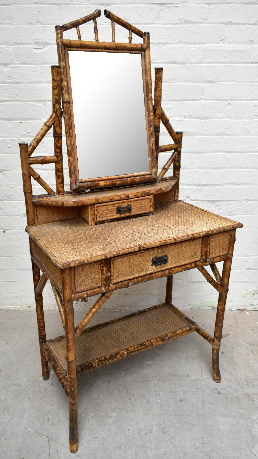 An early 20th century bamboo mirror back dressing table, with two drawers raised on column supports,