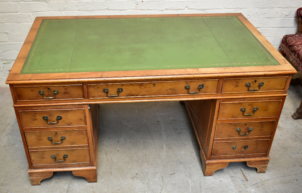 A reproduction yew wood pedestal desk, with green leather inset top above an arrangement of nine